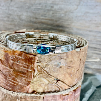 """This all Argentium Sterling Silver Rainbow Topaz is such a beautiful wire wrap gemstone bracelet. This faceted stone offers a soft blue hue of color with variations of pink going through it. Please keep in mind since this is a Heat Irradiated gemstone, no two are alike. Slight variations will occur with each one sent as a custom order. Our customers love our """"Treasures From Heaven Collection"""", and usually purchase multiples over time."""