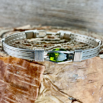 Shown is a Natural Peridot handcrafted with an Argentium Silver. This bracelet features a New Classic style wire wrap band. The price of this particular gemstone can vary considerably due to the quality of the stone. This gemstone is a VVS quality making it an excellent investment.