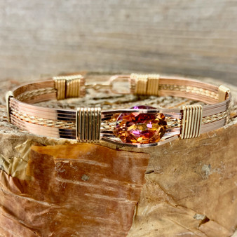 "CUSTOM create your next heirloom treasure from our ""TREASURES FROM HEAVEN COLLECTION"". Shown in Yellow and Rose Gold selection with a Classic style band with a Anastasia Topaz.  No need to decide what you need to be a STAND OUT, this bracelet will go with everything."