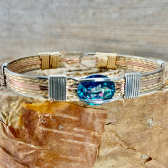 "CUSTOM create your next heirloom treasure from our ""TREASURES FROM HEAVEN COLLECTION"". Shown in Yellow, Rose Gold and Silver selection with a New Classic style band with a Rainbow Topaz.  No need to decide what you need to be a STAND OUT, this bracelet will go with everything."