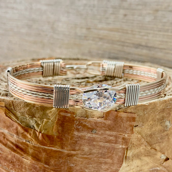 """Shown is a Tri-Metal 8 wire bracelet with a Classic style band. The Silver metal is so sweet, taking on a platinum patina when it oxidizes but never getting black. This tension mount gemstone is a simple yet elegant and very functional jewlery heirloom. Enjoy this """"Treasure From Heaven"""" for years to come."""