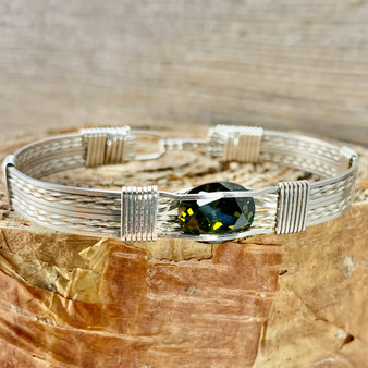 """Shown is an all Argentium Sterling Silver 8 wire bracelet with a New Classic style band with a Synthetic Peridot. This metal is so sweet, taking on a platinum patina when it oxidizes but never getting black. This is very compatible with white gold. Enjoy this """"Treasure From Heaven"""" for years to come."""