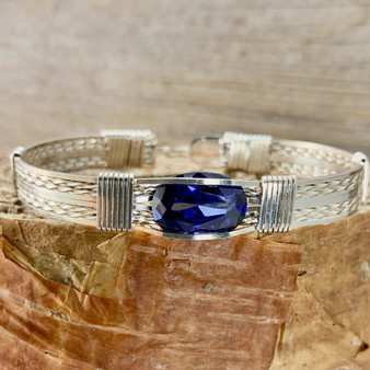 Who doesn't love Tanzanite? Shown is an all Argentium Sterling Silver Synthetic Tanzanite handcrafted on a New Classic bracelet band. Because this Tanzanite is a synthetic one, it is much more durable in this tension mount setting. Each one is MADE TO ORDER so you can create the exact combination you like.