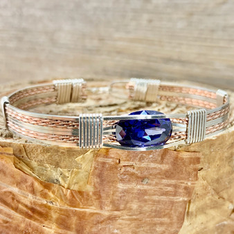 Who doesn't love Tanzanite? Shown is a Silver and Rose Gold Synthetic Tanzanite handcrafted on a New Classic bracelet band. Synthetic Tanzanite is much more durable in this tension mount setting than it's natural counterpart.