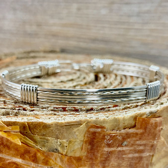 Shown is an all silver wire wrap bracelet made with Argentium Sterling Silver. This is a unisex metal bracelet that offers a split twist design we that call a New Classic. We create with the finest material available to insure that you will own a true heirloom treasure.