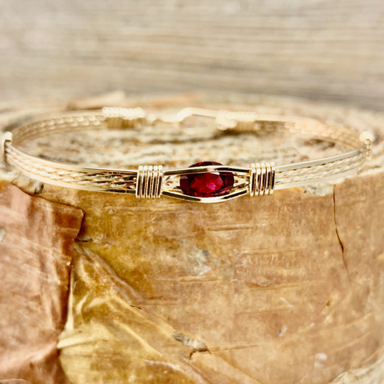 This synthetic garnet in an all yellow gold classic band is such a beautiful bracelet.  This can be custom created by go to the CUSTOM tab for a different metal or design as well as a special finished size.