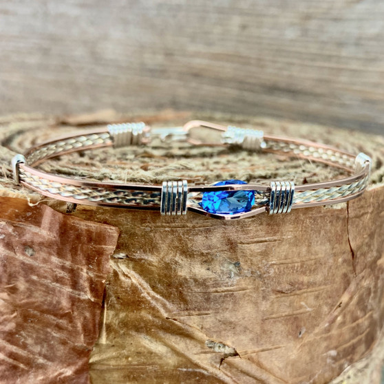 IN STOCK is a Rose Gold and Argentium Sterling Silver bracelet paired up with silver wrap wires. This striking Kashmir Blue Topaz makes a wonderful addition to anyones jewelry accessories.