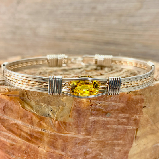 Shown is a Synthetic Golden Topaz wire wrap bracelet paired up with an Argentium Silver and Rose Gold classic bracelet band. We handcraft each one to suit your needs. We have been in business since 1993, handcrafting jewelry that is beyond ordinary.