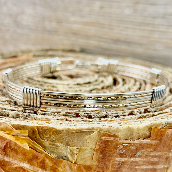 Shown is an all silver wire wrap bracelet made with Argentium Sterling Silver and Yellow Gold accent. This is a unisex metal bracelet that offers a split twist design we that call a New Classic. We create with the finest material available to insure that you will own a true heirloom treasure.