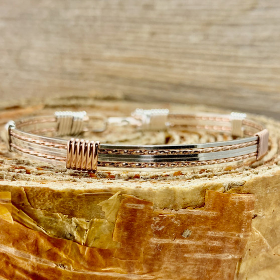 Shown is an all silver wire wrap bracelet made with Argentium Sterling Silver and Rose Gold accent. This is a unisex metal bracelet that offers a split twist design we that call a New Classic. We create with the finest material available to insure that you will own a true heirloom treasure.