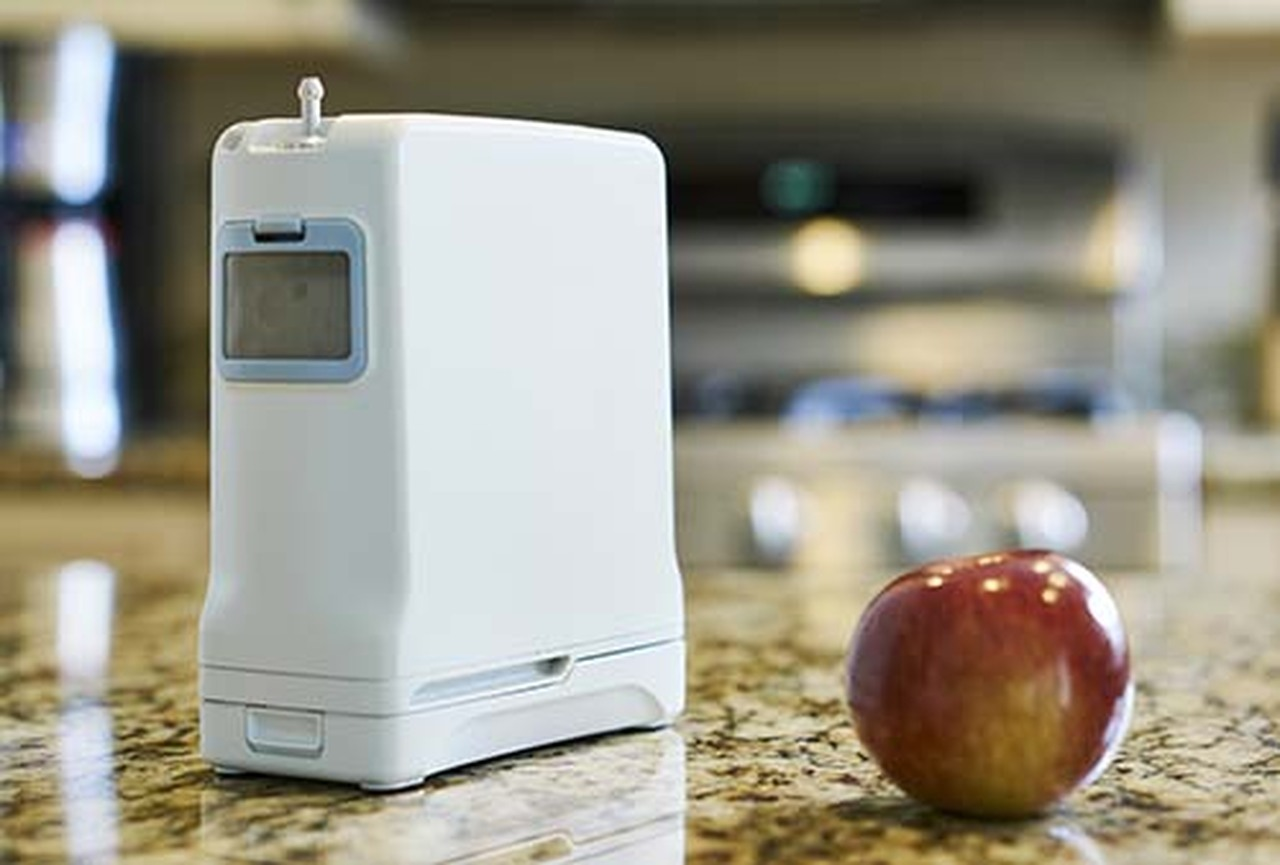 Inogen One G4 portable oxygen machine small size next to apple