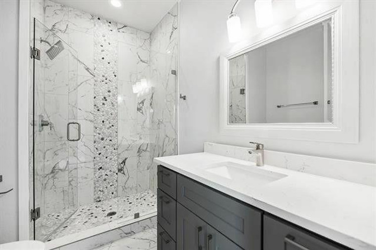 Complete Shower Remodel with Statuary Venato Tile and Black and White Pebbles