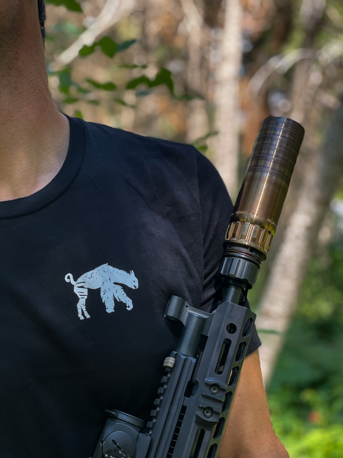 Picture of the Abel Company branded shirt being worn in the forest. The front of the shirt is in view with the focus on the Abel Creature. The person in the picture is holding up a rifle that has an Abel Company suppressor mounted on it.