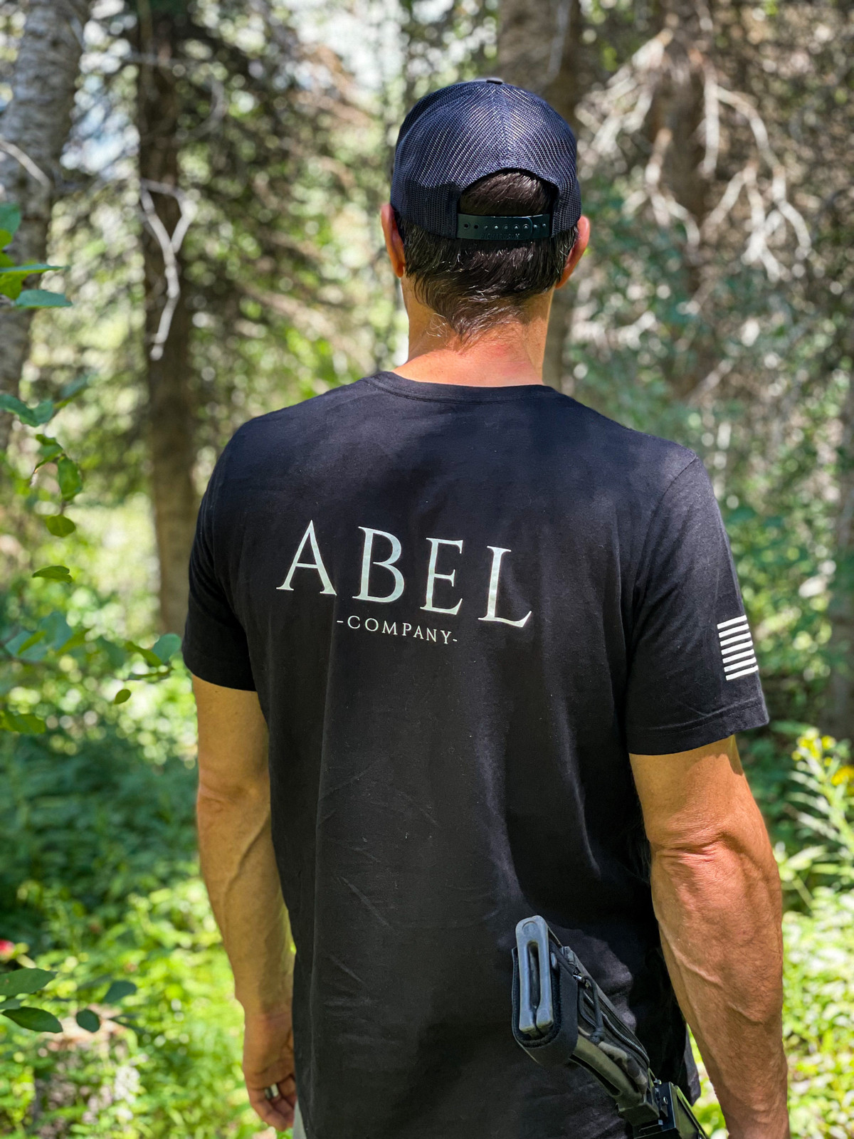 Picture of the Abel Company branded shirt being worn in the forest on a man with a SnapBack hat - the back of the shirt is in view.