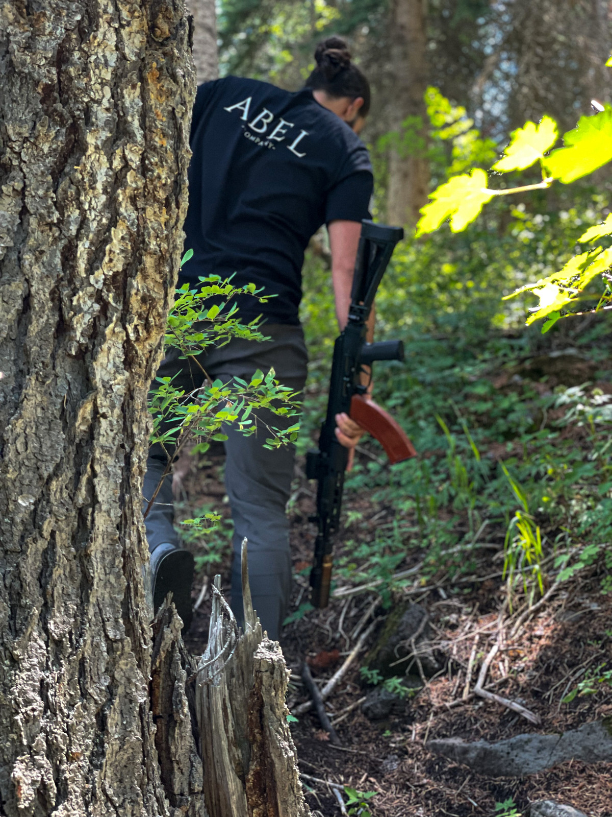 Picture of the Abel Company branded shirt in the forest on a man holding a rifle - the back of the shirt is in view.