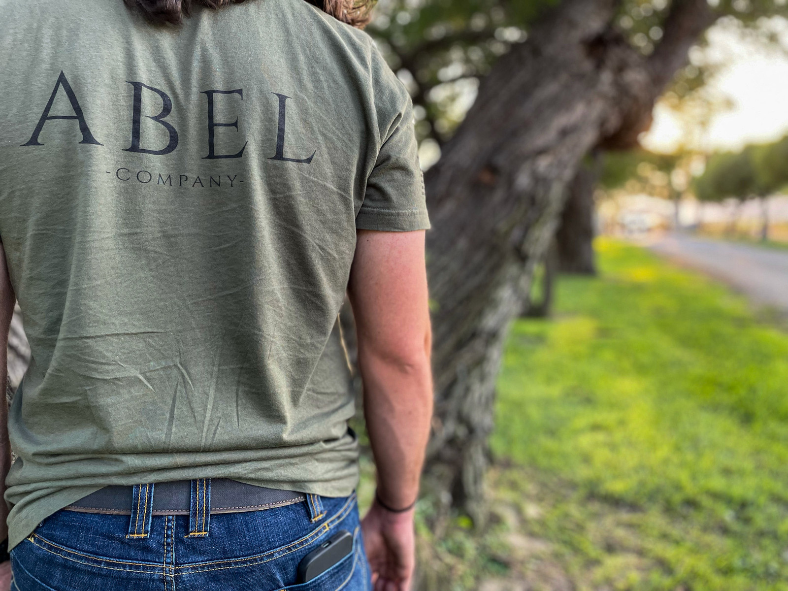 Picture of the green Abel Company branded shirt being worn in front of trees