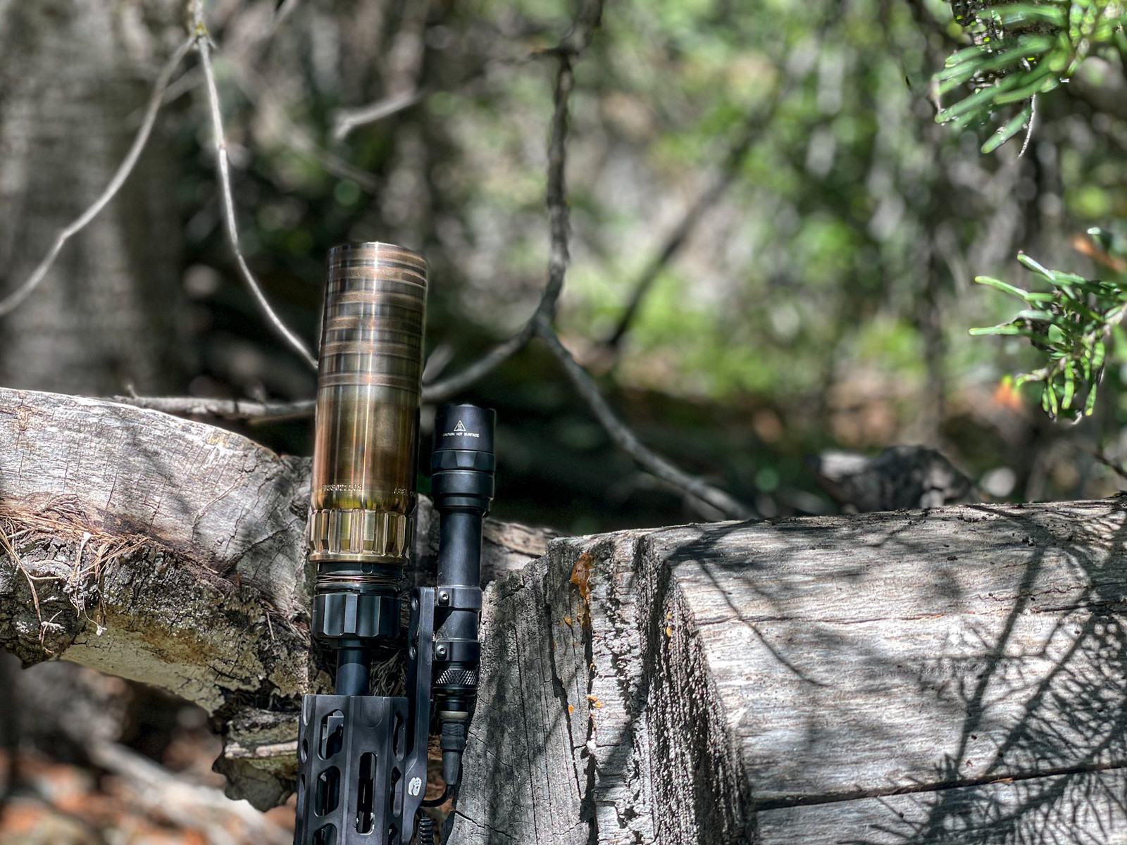Picture of Abel Company's Biscuit mounted on a firearm leaning up against a log in the forest.