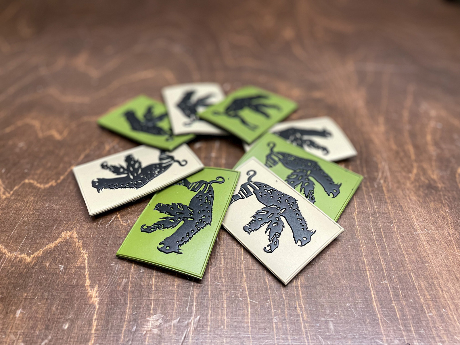 Picture of OD Green and FDE patches of the Abel Creature, laid out in a round configuration on a work bench.