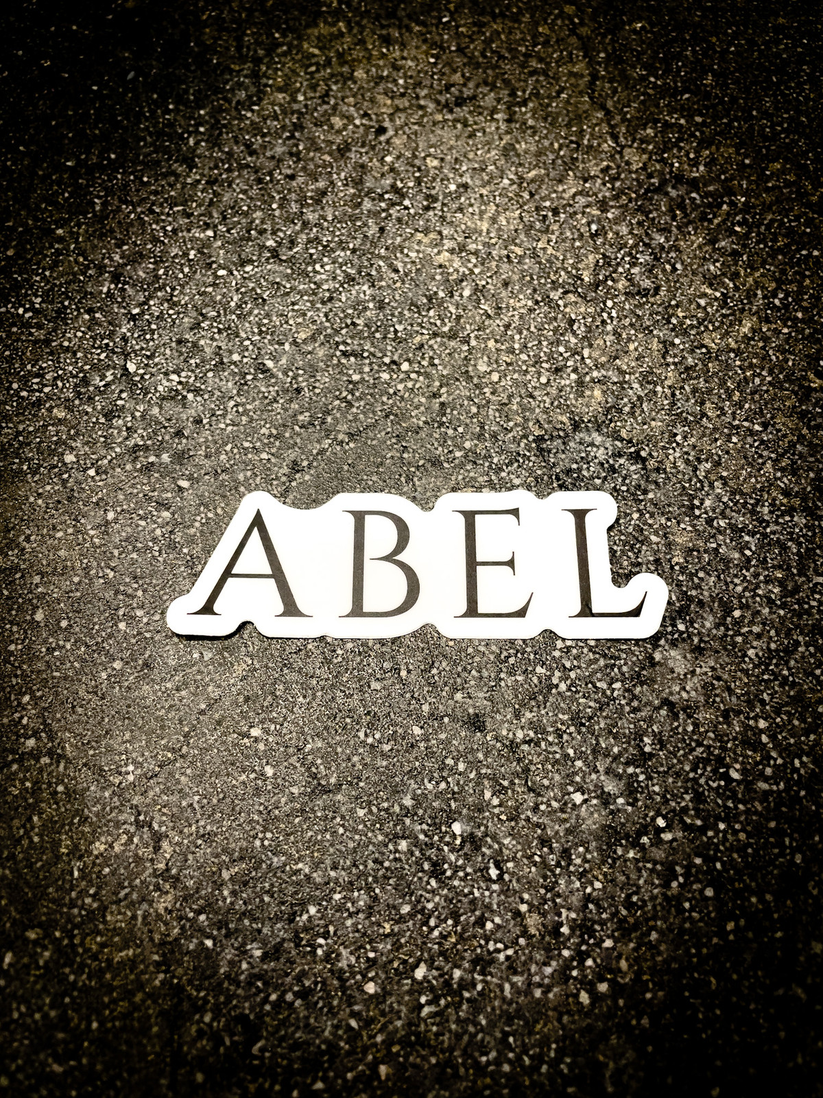 Abel Company brand sticker on concrete background, black ABEL typeface on white contrast