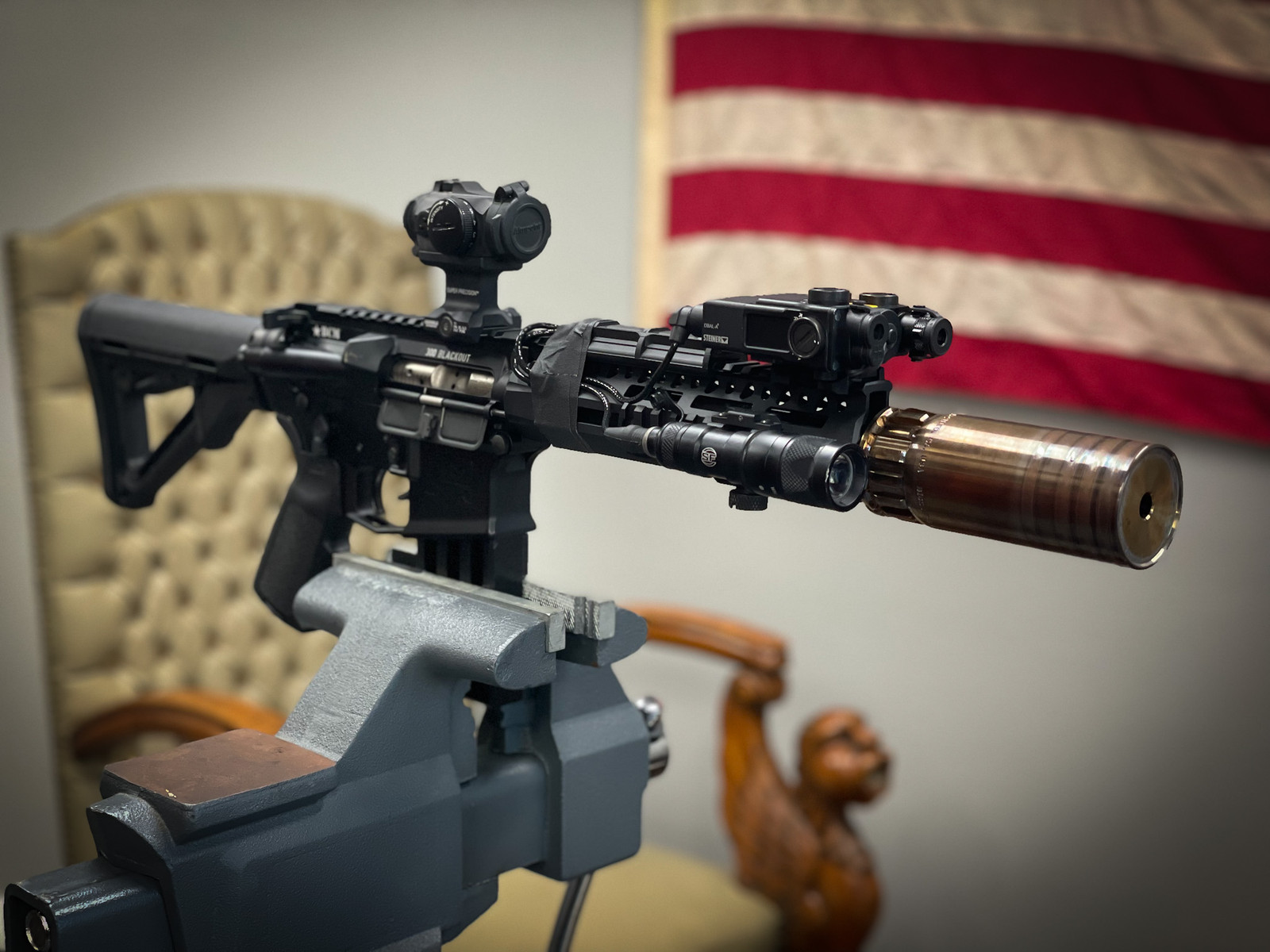 Biscuit suppressor mounted on a rifle with American flag background.