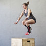 Julie Foucher wearing pink ( small / medium sized ) shin guards while box jumping.