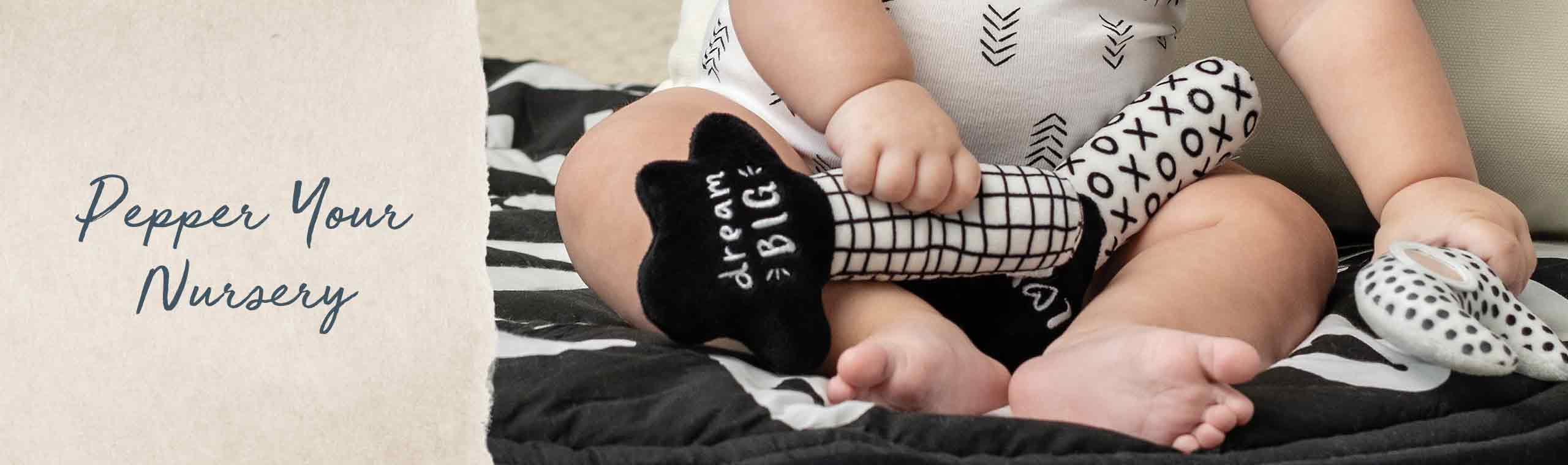Pepper your Nursery! a baby wearing black and white socks, clothes and playing with a blank and white toy