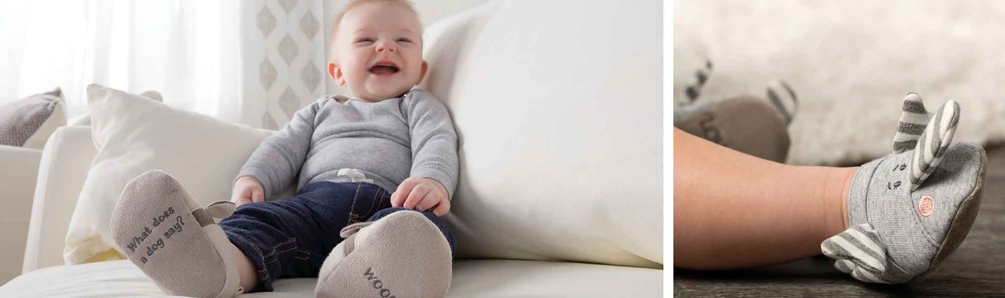 a baby laughing and wearing a pair of baby boots