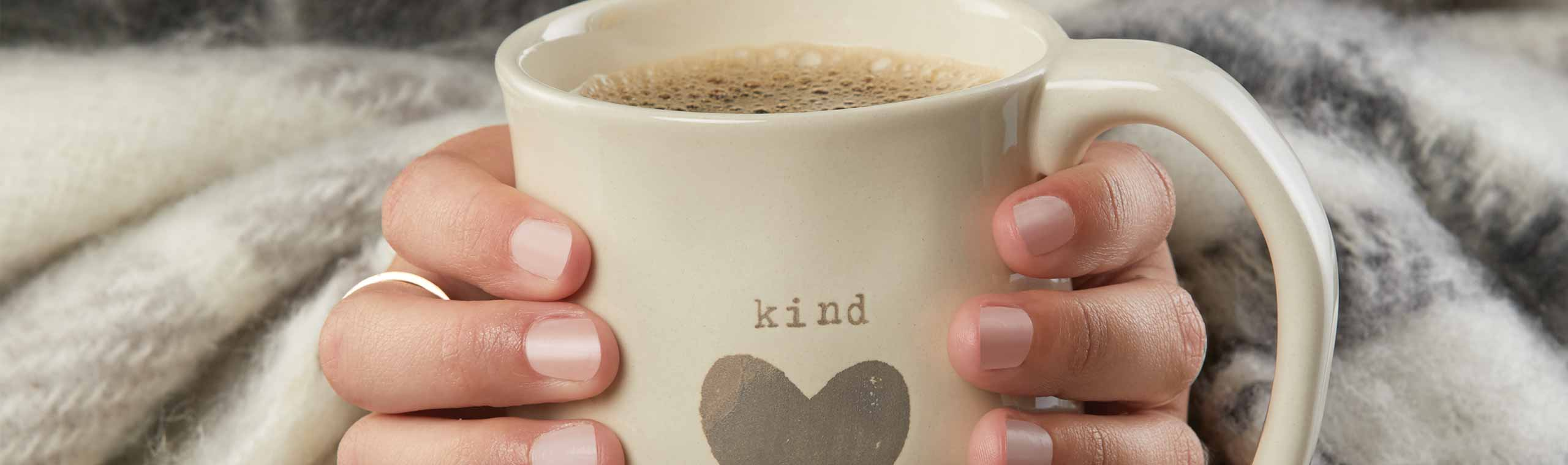 a cup of hot coffee with a message that says be kind with a heart underneth