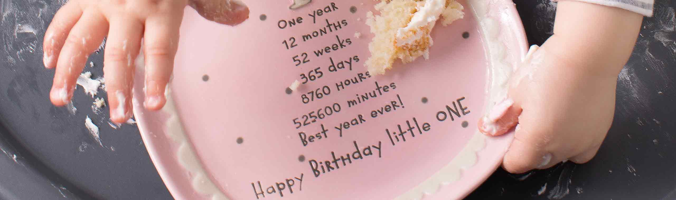 a baby eating cake on a pink plate about a babys first birthday