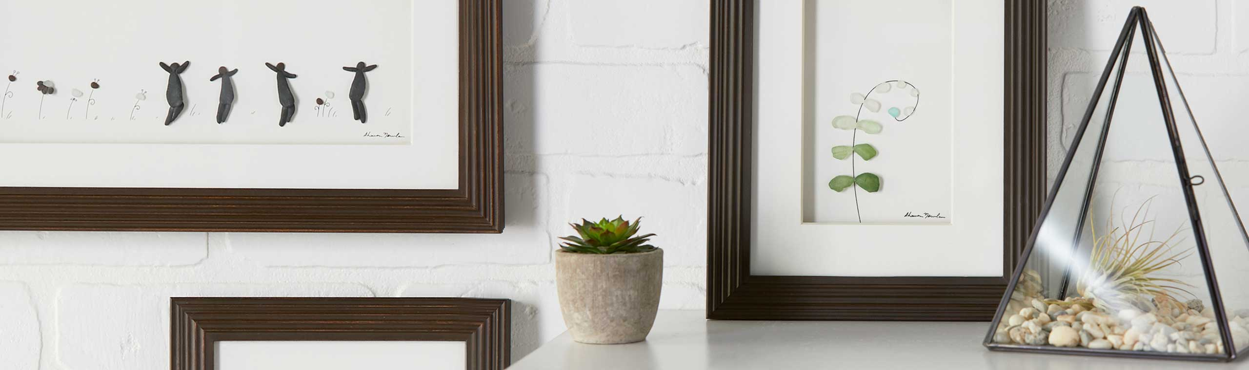 small plants on a table and hanging picture frames with stone illustrated pictures