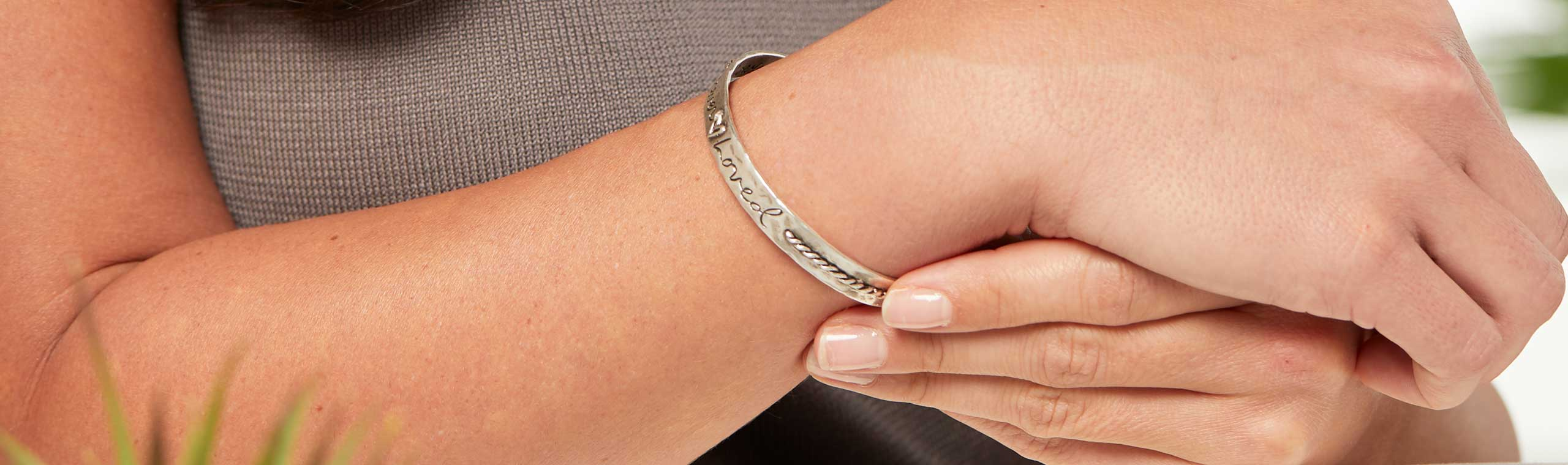 Close up of a women wearing a metal bracelet with the words engraved love