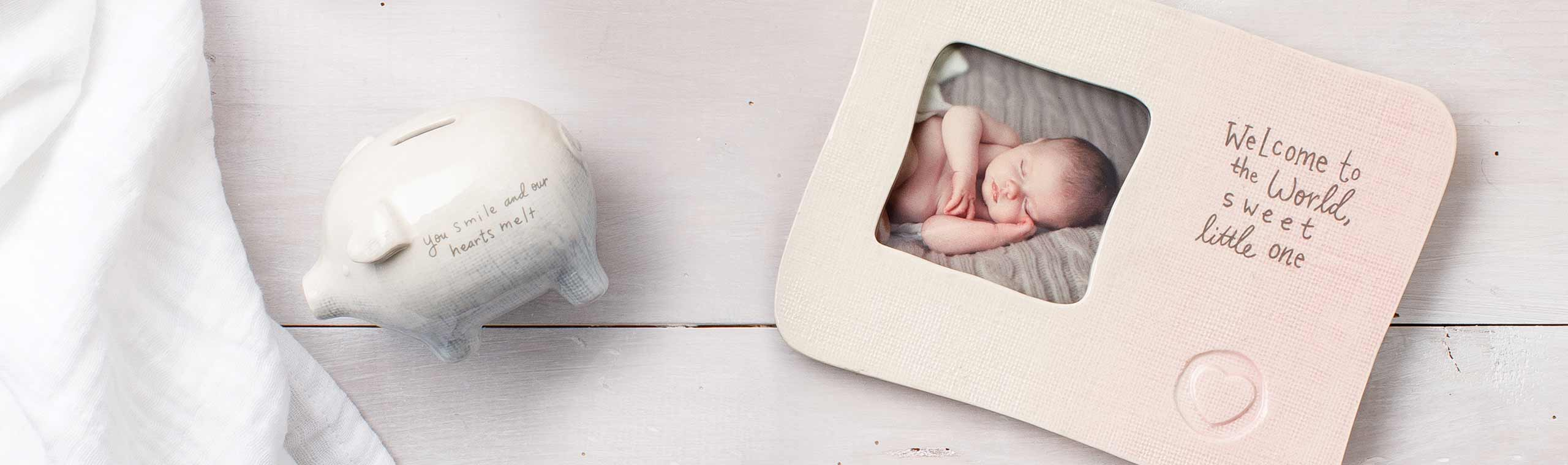 a ceramic piggy bank and a baby frame with a baby sleeping