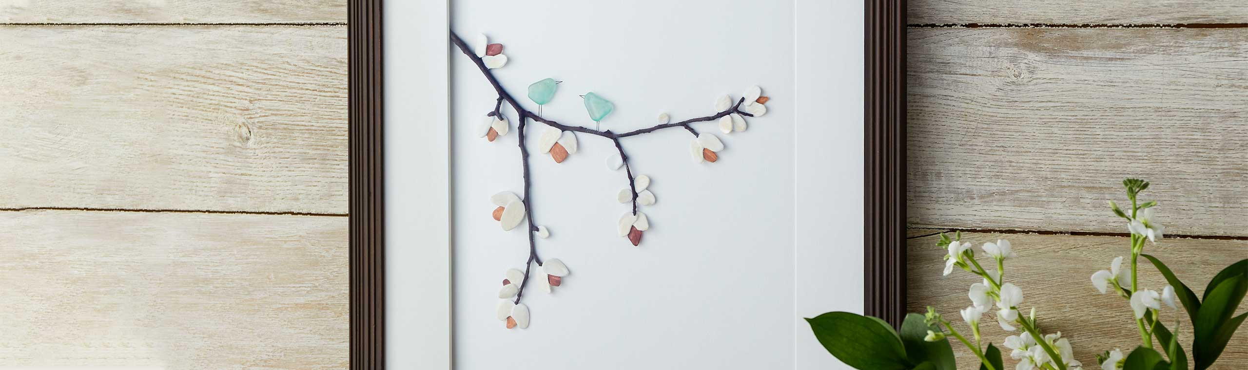 Wall art frames with little stones that make u a picture of birds on a branch