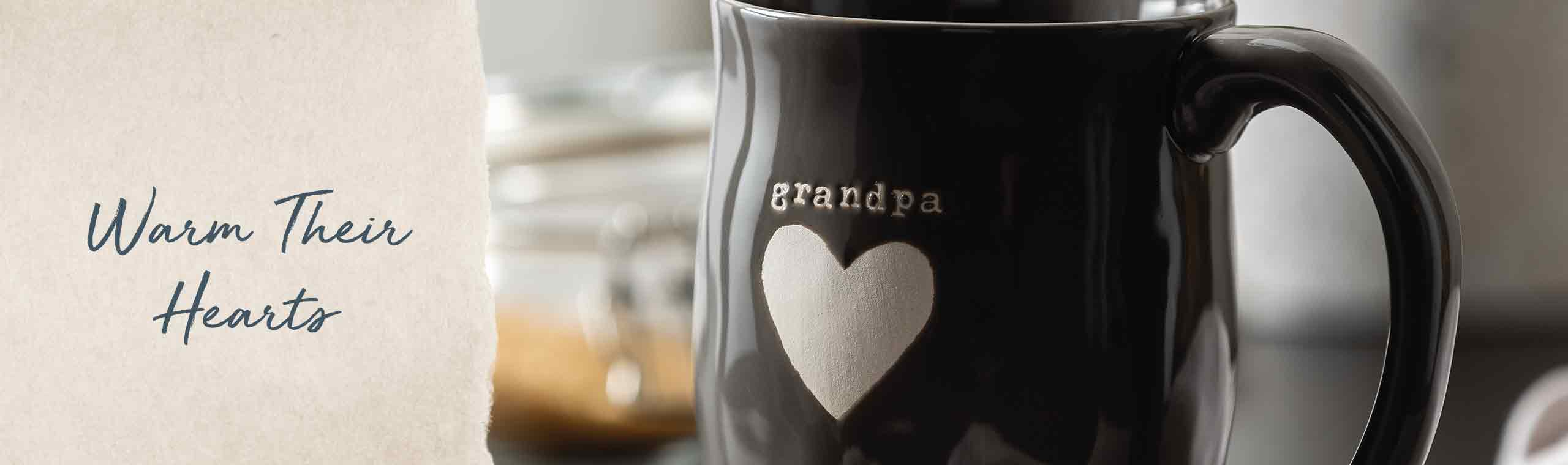 Warm their hearts. black mug with grandpa in a script font printed with a heart