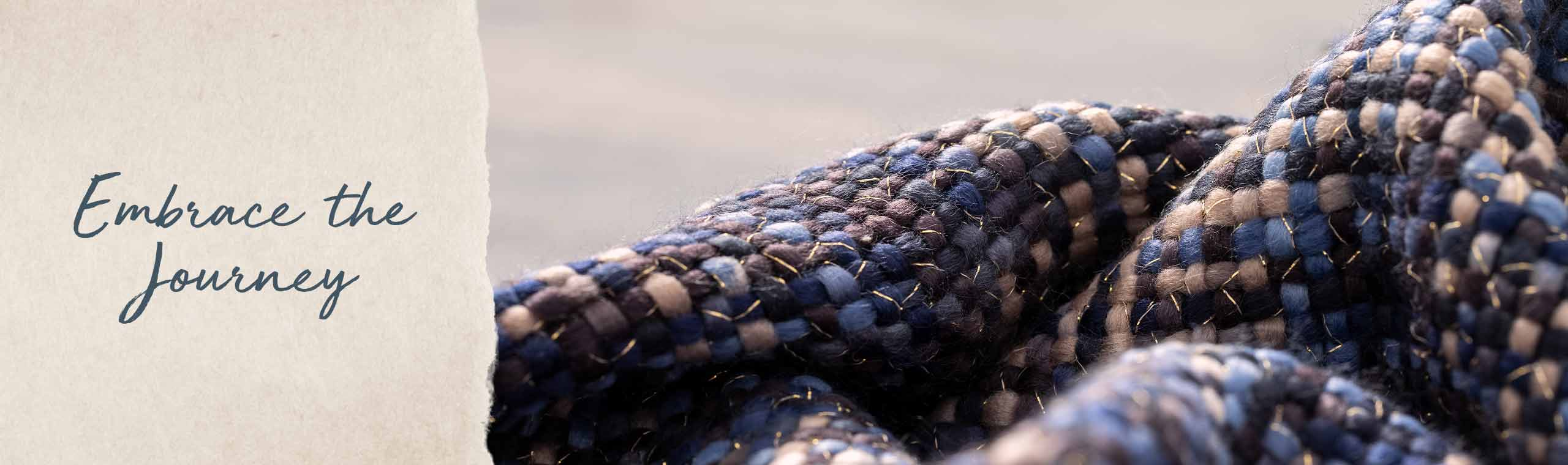 Embrace the journey. close up of the blue texture of a blue woven scarf with gold threads