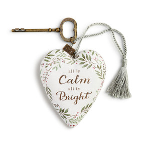 A white art heart with a green floral print, a silver tassel, and a bronze key.
