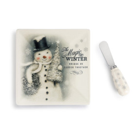 cutting board with snowman and Magic of Winter printed on it next to cheese knife