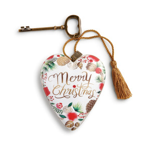 Small white heart pendant with 'merry christmas' in gold surrounded by red flowers, brown pinecones, green branches - gold key and tassle attatched