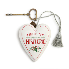 """A white art heart with """"meet me under the mistletoe"""" in red and green font, a bronze key, and a silver tassel."""