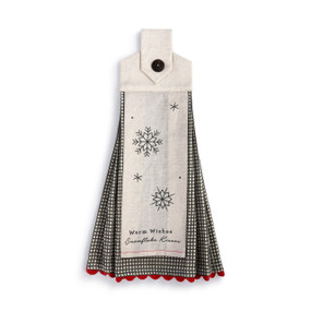 A black and white plaid tea towel with red scalloped edges and snowflakes and a winter message on the front.