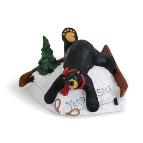 Black bear figurine laying on white rock with green treen - rock says 'yard sale' in blue