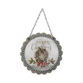 Front view of silver round ornament with 'merry christmas' on it above silver wreath
