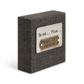 """A black woven plaque with a silver card that reads """"think... plan... make it happen!""""."""