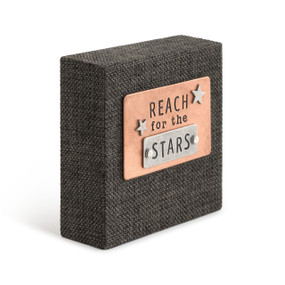 """A black woven plaque with a copper card that reads """"reach for the stars""""."""