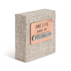 """A gray woven plaque with a copper card that reads """"One life. Lots of possibility.""""."""