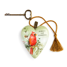 """A textured green and white Art heart with a painting of a red cardinal on a pine branch, and reads """"always and forever"""". With a bronze key and gold tassel."""