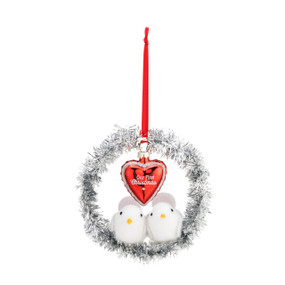 """A small silver tinsel wreath ornament with two small white doves, a small red heart that reads """"our first Christmas', and a red ribbon string."""