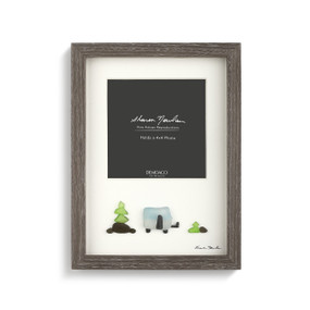 A gray wooden picture frame with an ivory backing, and a pebble scene of a car at a road sign. Filled a gray and white product slip.