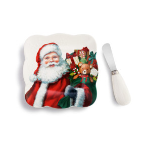 A white spreading plate with an image of Santa holding a large green sack filled with presents. Placed beside a matching white spreading knife.