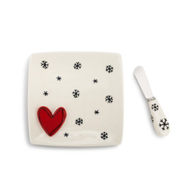 A cream spreading plate with black snowflakes and a red heart. Placed beside a matching spreader knife.